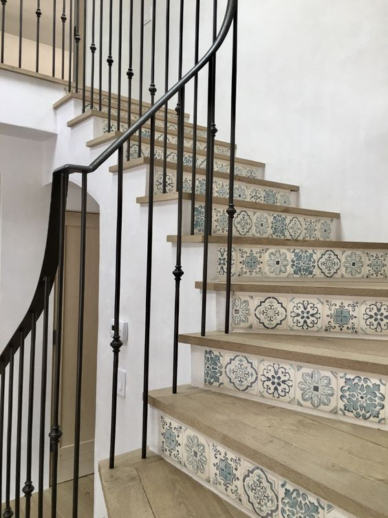 Blue and white handpainted Mediterranean tiles on stair risers in breathtaking beach house on Hello Lovely Studio