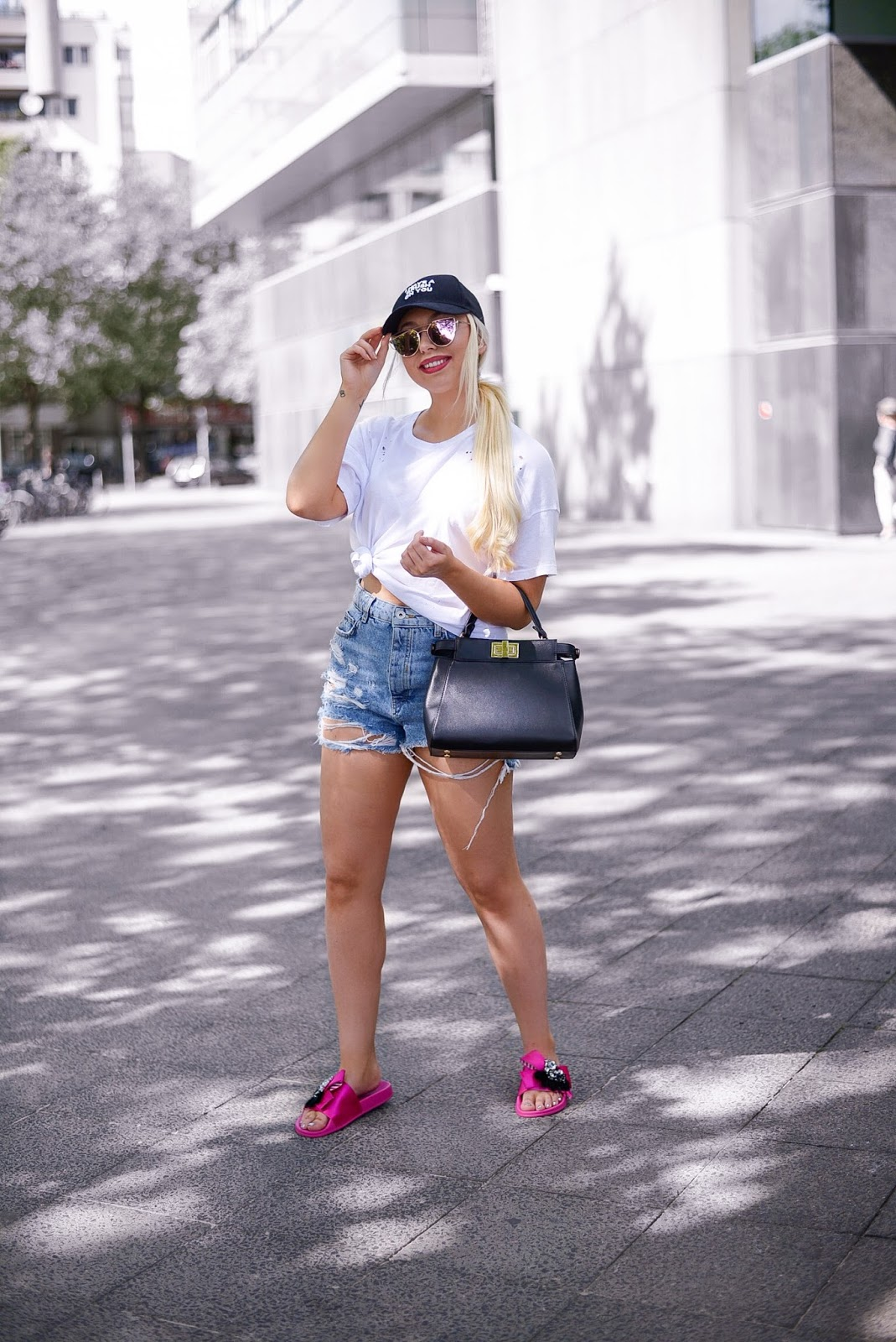 city summer outfit ideas_black cap_ripped denim shorts_white tee