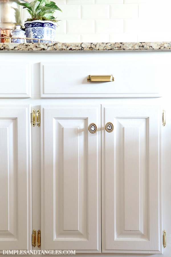 brass cup pulls, polished brass hinges, white cabinets