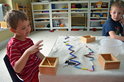 child with Montessori addition snake game and a very long snake