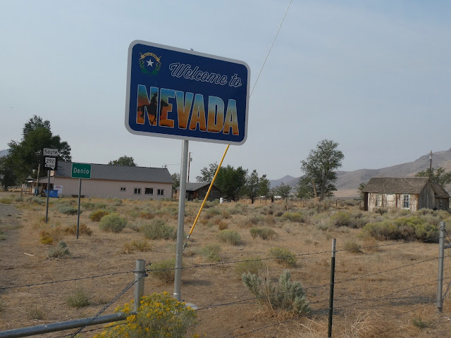 Nevada welcome sign foreground, general store and shacks background, sagebrush in between