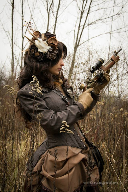 Woman in steampunk clothing in shades of brown, carrying a steampunk gun, wearing a fascinator with a animal skull