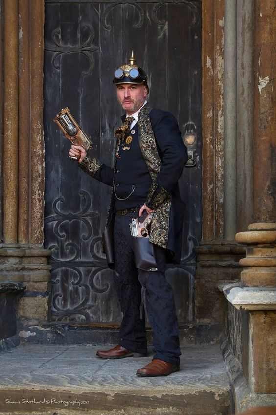 Man wearing steampunk clothing in black and gold. coat, waistcoat, ascot/tie, guns, hat, goggles. Men's steampunk costumes and clothing
