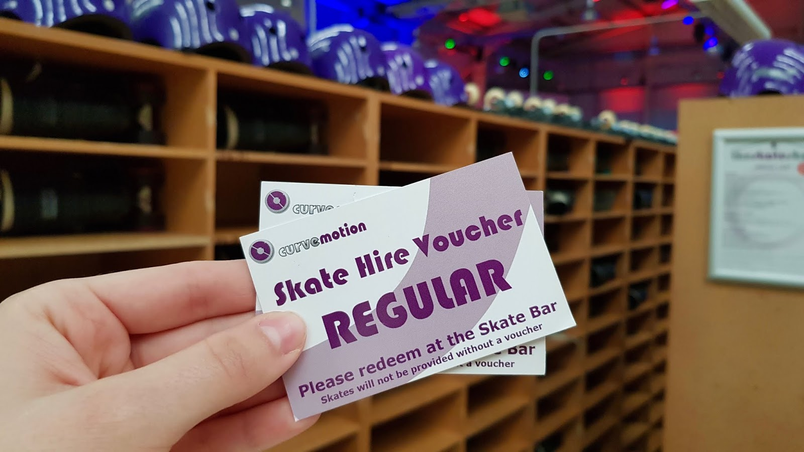 A close up of CurveMotion skate hire tokens, with racks of skates in the background