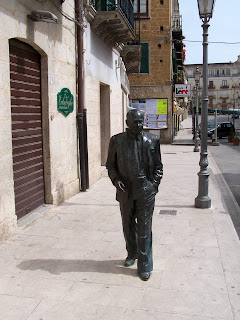 A statue of Leonardo Sciascia, cast in bronze,  on Via Garibaldi in his home town, Racalmuto