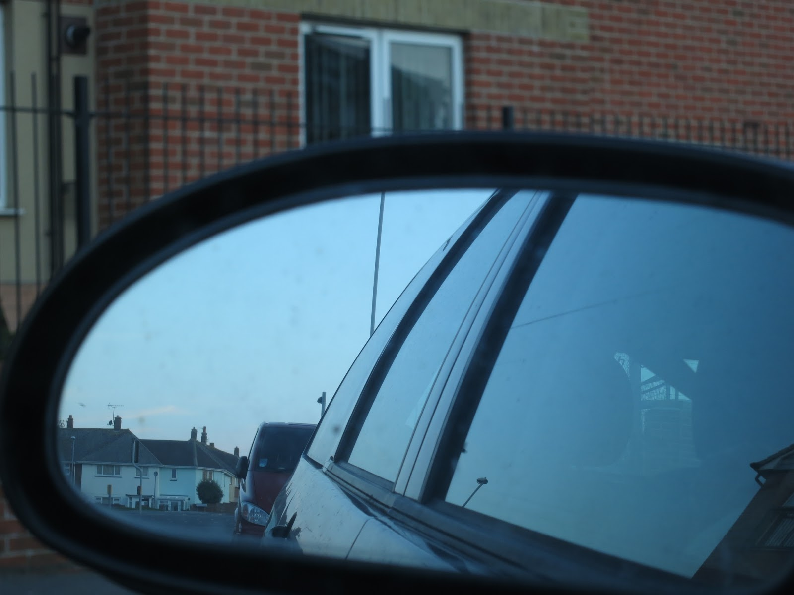 White houses with grey tiled roofs reflected in mirror of car parked in front of red bricked flats