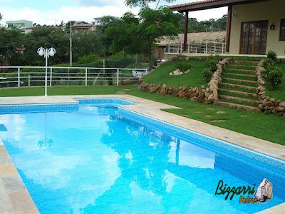 Construção de piscina de concreto com o revestimento de pastilha, o piso do passeio da piscina com pera São Tomé, as muretas de pedra, a escada de pedra e o peitoril de alumínio na piscina.