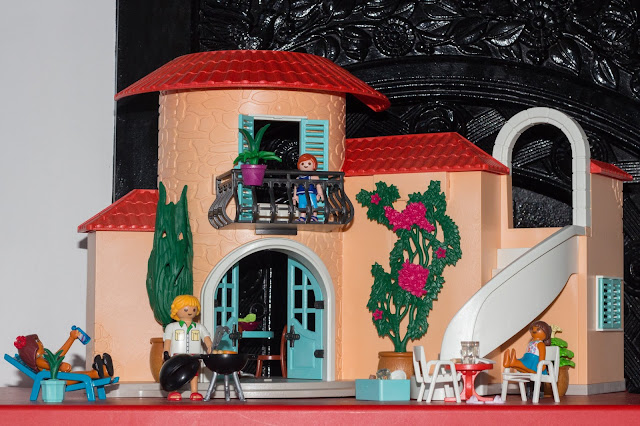 The front view of the Playmobil summer villa with a child at a table, another on the balcony, dad barbecuing and mum on the sun lounger