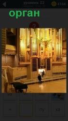 В большом помещении находится концертный орган, на котором играет музыкант и рядом стоит его руководитель