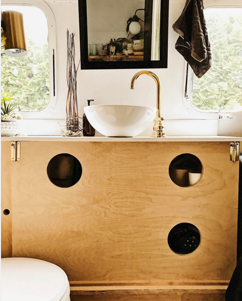 natural wood, cozy lighting, and plants fill the tiny bathroom of a vintage airstream