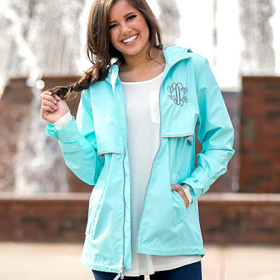 aqua monogrammed rain jacket in front of fountain