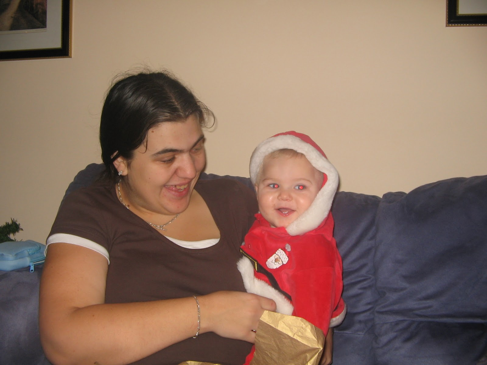 a photo of Jen holding ben as a baby, jen is in a brown top and smiling. Ben is in a santa outfit. Jen is sitting on a blue sofa.