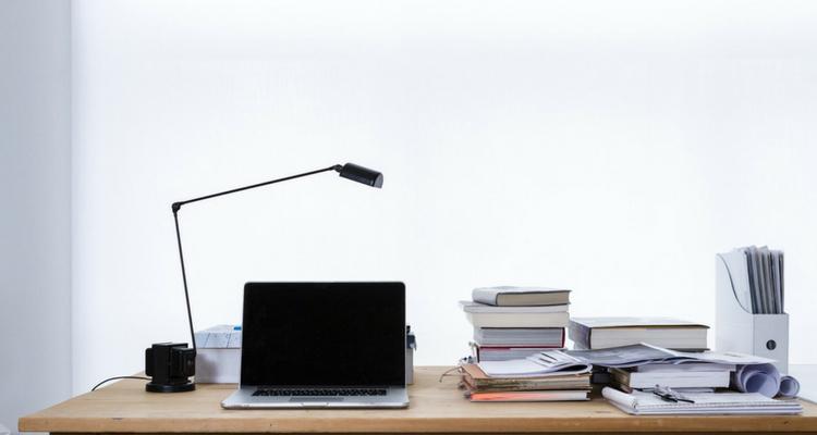 Laptop na biurku z licznymi papierami, w tle jasne światło.