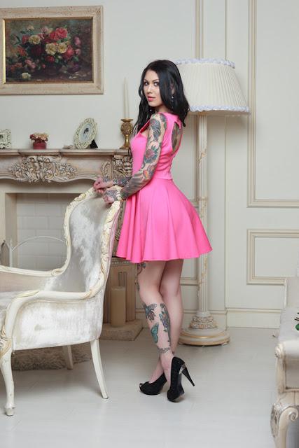 Tätoweirte Frau aus Russland im Minikleid mit Higheels