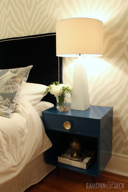 blue bedside table with white lamp and flowers
