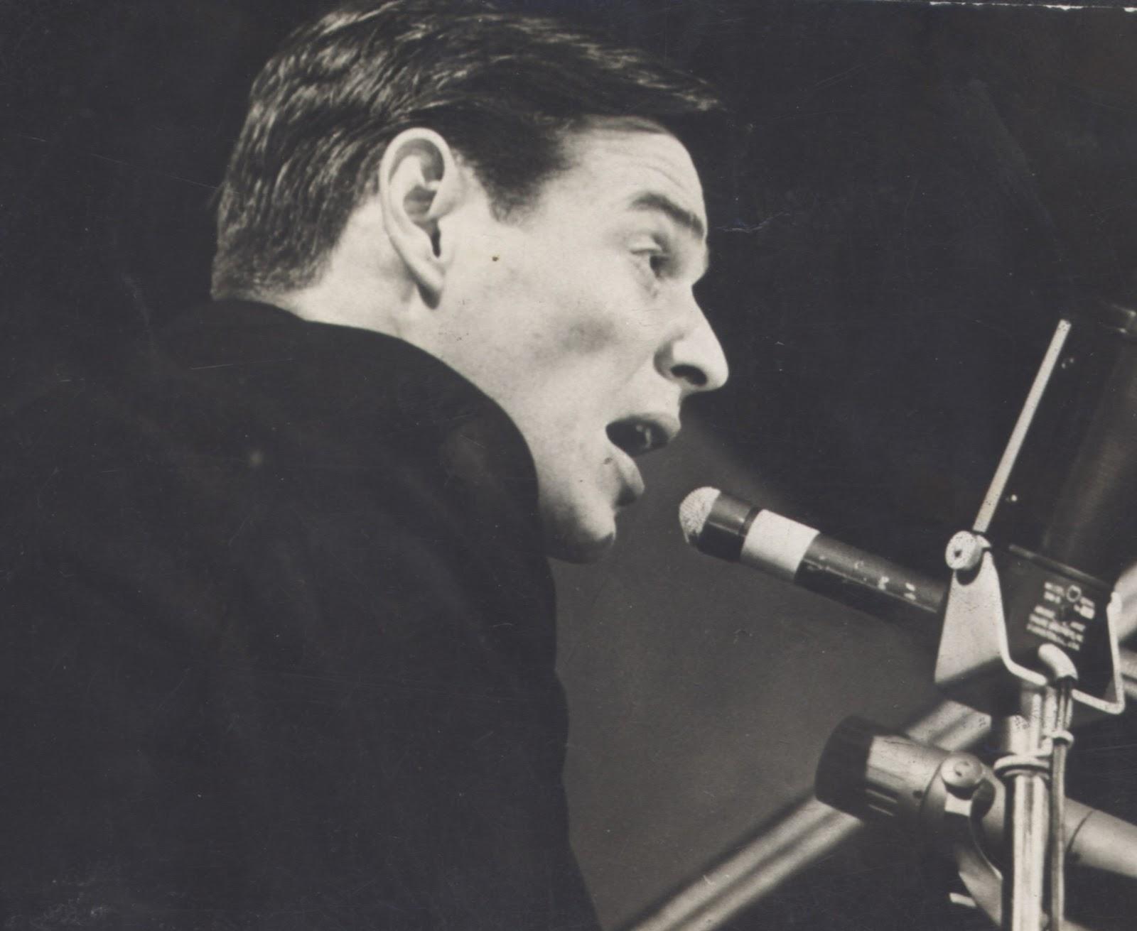 マイクで歌を歌うトム・ジョビンの顔