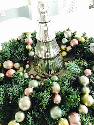 Christmas wreath with silver tree in middle with pastel garland