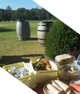 Foreground - our picnic lunchboxes of potato salad, green salad, sliced bread, turkey and watermelon.Looking out onto lawns with a rosemary bush and two winebarrels in the middle ground and trees in the distance against a blue sky.