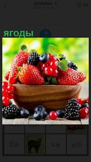 на столе в чашке лежат спелые ягоды, малина и клубника