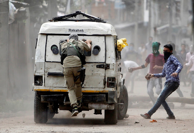 Image Attribute: Demonstrators try to hurl stones at an Indian police vehicle during a protest in Srinagar against the recent killings in Kashmir, August 30, 2016. REUTERS/Danish Ismail/File Photo