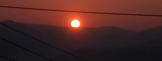 The sun rises above the ridge