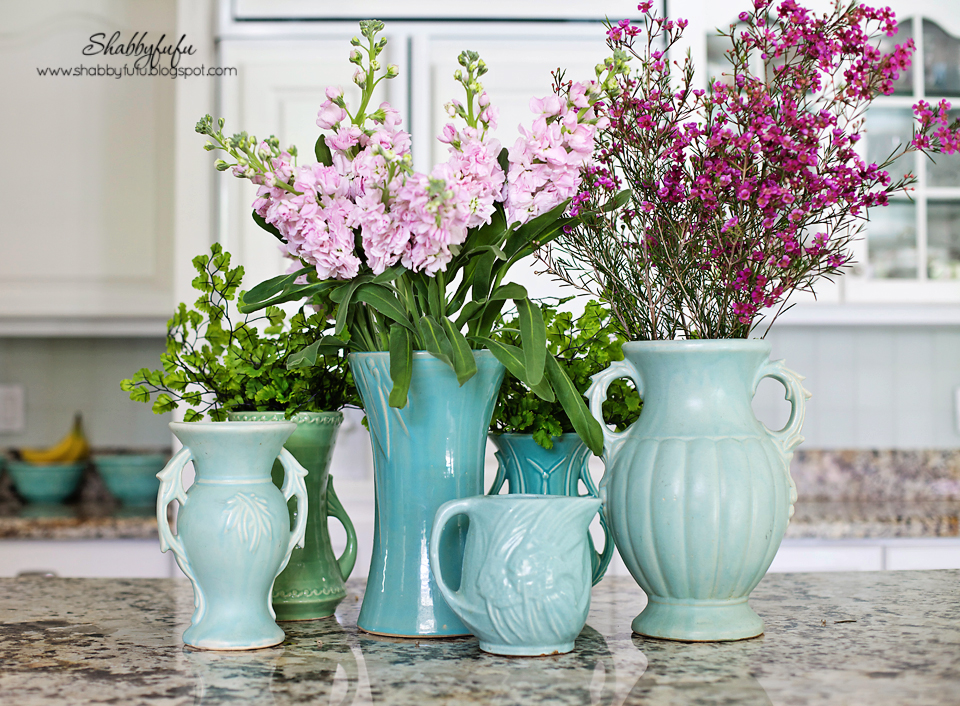 Adding pops of color to a room - these pink and green flowers in teal vases add color to a white kitchen