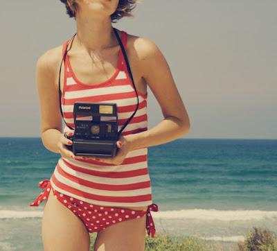 Fotografia de mujer en la playa con bikini rojo y lunares blancos