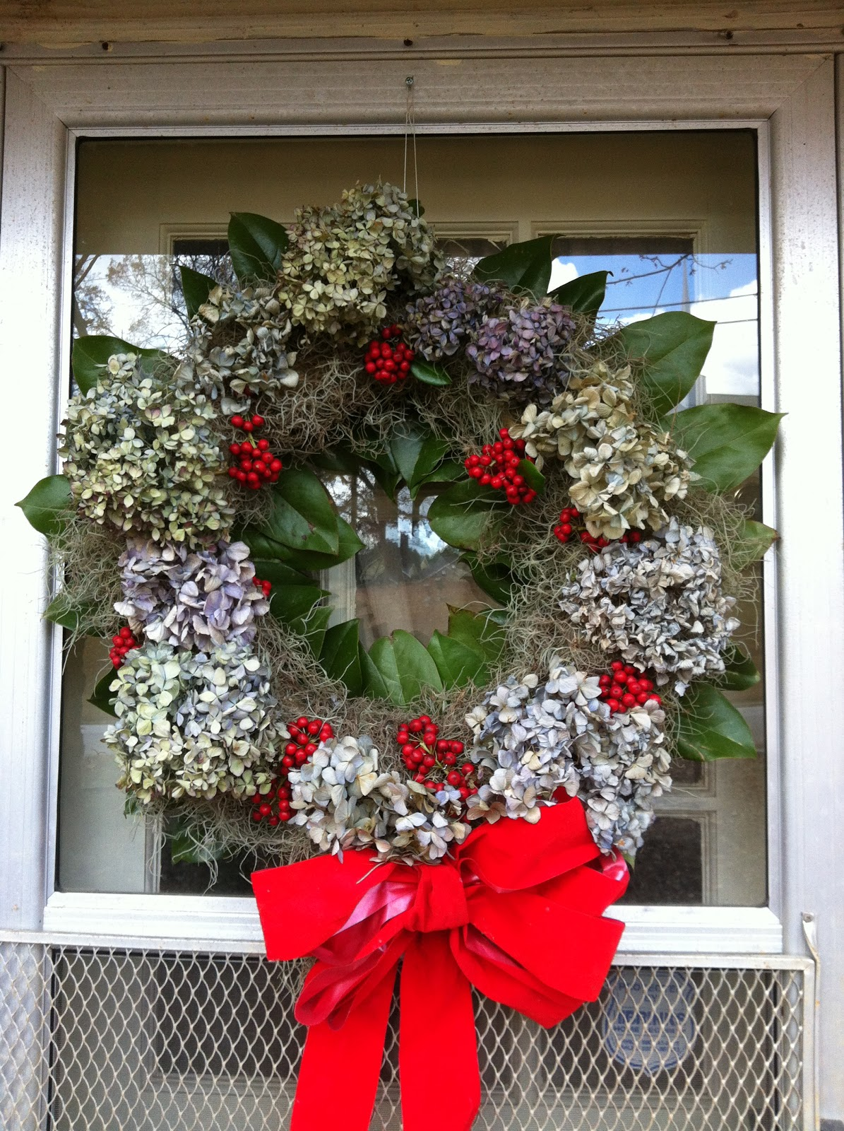 A Red Velvet Christmas Bow Completed The Wreath Hanging Outside Of Our Storm Door