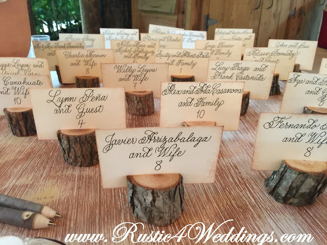 Rustic Tree Branch Place Card Holders Alongside Some Tree Branch Pens