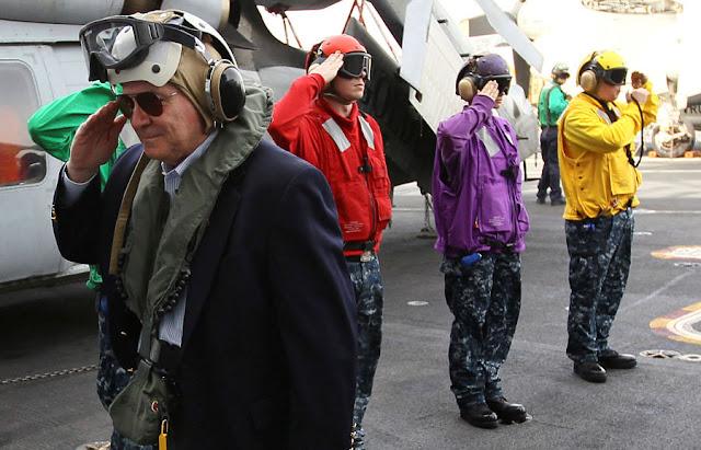 FILE PHOTO: U.S. Secretary of Defense Robert Gates (L) salutes an honor cordon as he arrives aboard the USS Abraham Lincoln in the Arabian Sea December 6, 2010. REUTERS/Win McNamee/Pool/File Photo