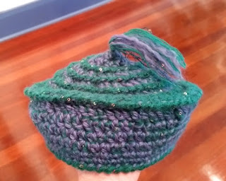 Muffin-shaped beret crocheted in mauve and teal. Wisps of unplied fibre close the top round.