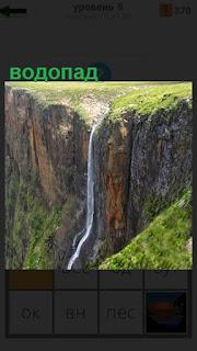 С высоко крутого обрыва течет водопад вниз