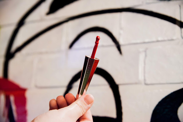 Fenty Beauty's Stunna Lip Paint's applicator in front of a grafitti background