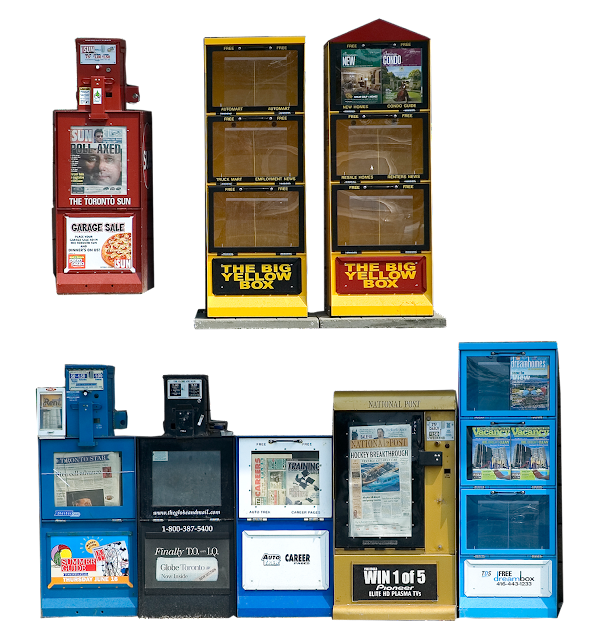 A variety of newspaper vending boxes, of the type usually found outside public places, and on streetcorners.