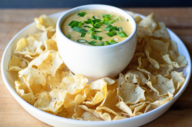 The queso, in a bowl, on a platter, with chips