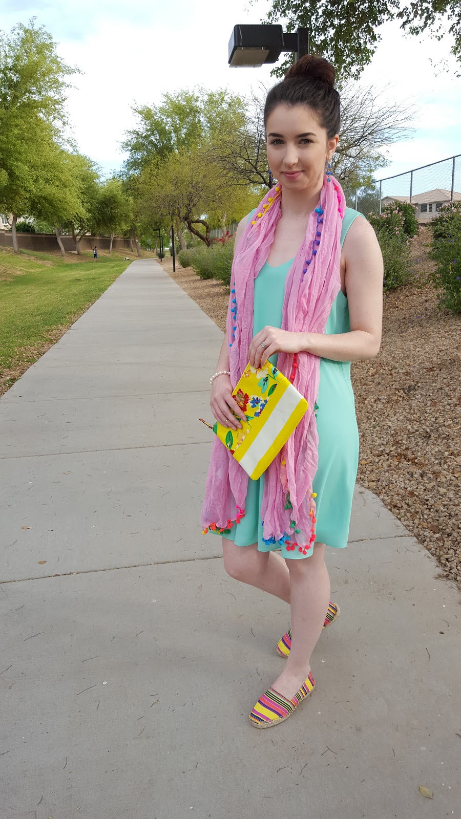 Pair a bright flowy dress with a colorful pompom scarf and espadrilles