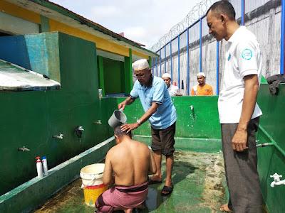 Muslim Harianjaya melakukan mandi taubat dibantu oleh imam masjid An-nur
