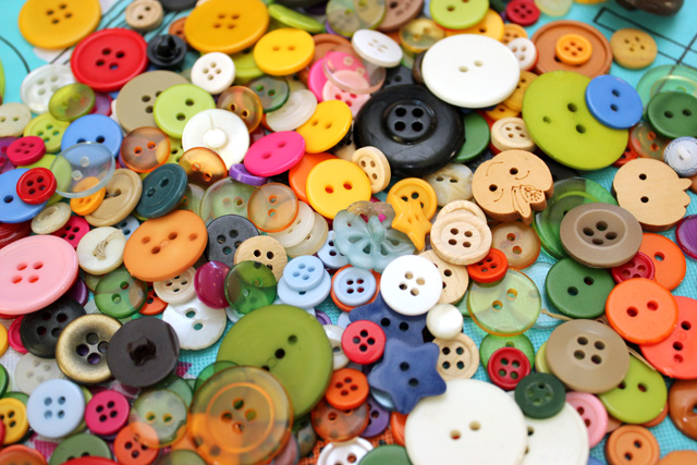 Pile of multi color and sizes of buttons for creating button art