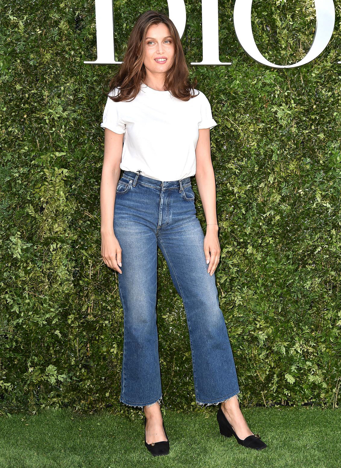 French Outfit Idea — Laetitia Casta in a white t-shirt, raw-hem flared jeans, and black square-toe heels