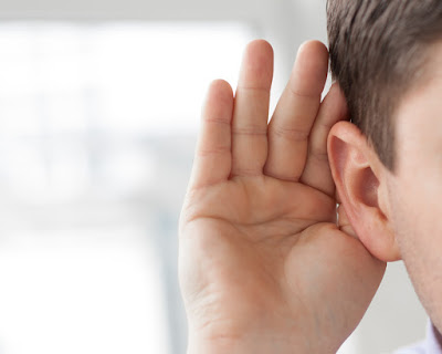 A close-up of a man with his hand cupped to his ear for better hearing