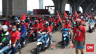 Ratusan massa Konfederasi Persatuan Buruh Indonesia (KPBI) Jakarta menggelar aksi di depan pintu masuk JICT 1, Pelabuhan Tanjung Priok, Jakarta Utara. (CNN Indonesia/Jonathan Patrick)