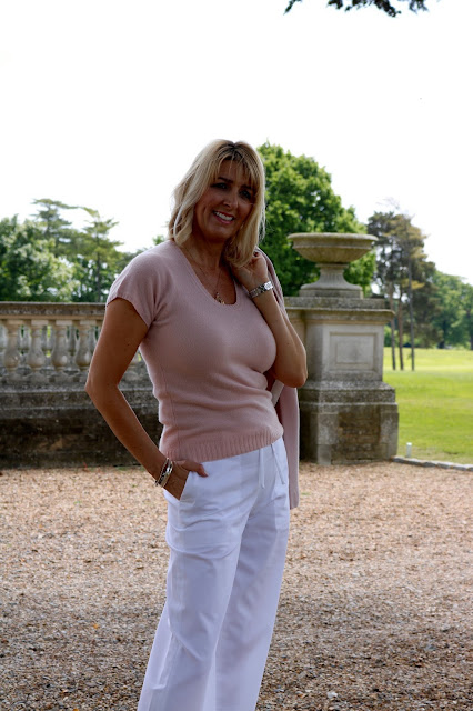 blush pink jumper and white trousers