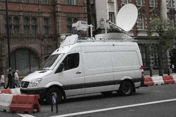 white media van with antenna and dish on top