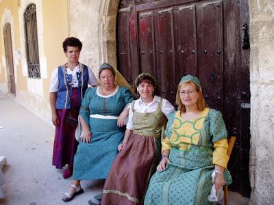 Mercado Medieval de Gumiel de Izán: cuatro damas medievales sentadas ante puerta con arco de medio punto