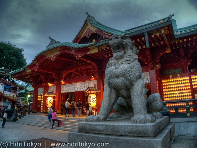 main hall of Kanda-Myojin. many Japanese lanterns were lighted. a massive stone guardian dog in front of the hall.