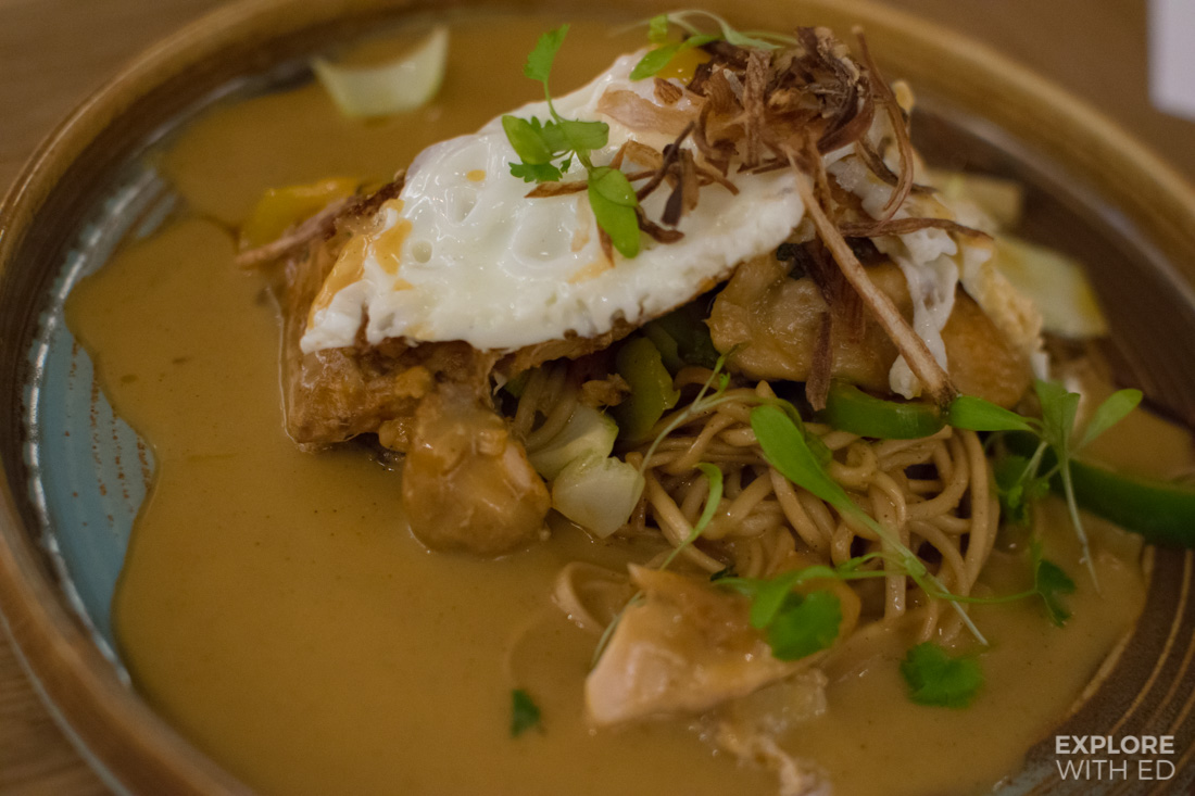 Chicken laksa with egg noddles stir fried vegetables and topped with a fried egg