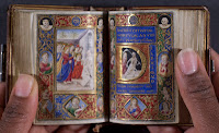 An open, miniature book of hours with densely painted and illuminated illustrations.