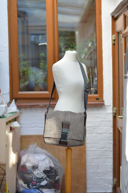 A handmade cross-body bag hanging from a mannequin