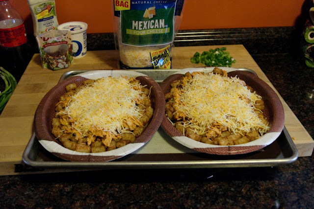 A picture of the two football plates, on a baking sheet, filled with tater tots, chicken mixture, and shredded cheese.
