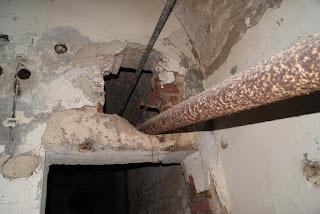 Eine Türöffnung. Über der Öffnung klafft ein großes Loch, duch das ein altes Heizungsrohr verläuft
